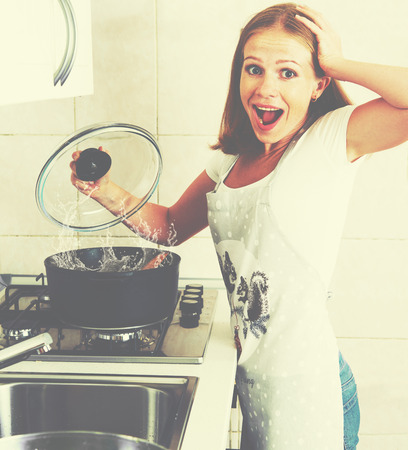 disaster: funny woman housewife prepares in the kitchen. burnt food