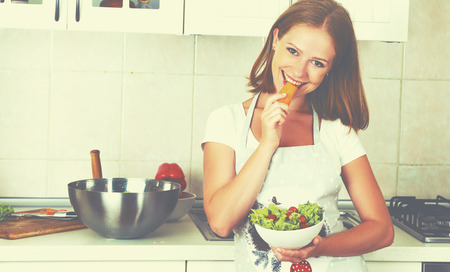 young woman smiling: young happy woman eats vegetable vegetarian salad on kitchen