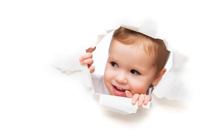 sorpresa: Bebé divertido niño mira furtivamente a través de un agujero en un cartel de papel blanco vacío