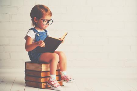 personas leyendo: niño niña feliz con gafas de leer un par de libros Foto de archivo