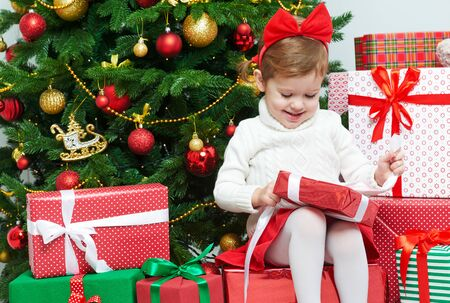 opens: happy child girl opens Christmas gifts near a Christmas tree