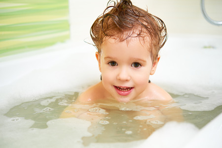 little girl bath: happy child toddler girl bathes in a bath with foam and bubbles