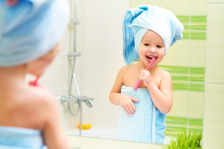 funny little girl cleans teeth with a toothbrush in the bathroom