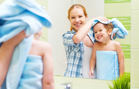 shower head: happy family in the bathroom. mother of a child daughter with a towel dry hair