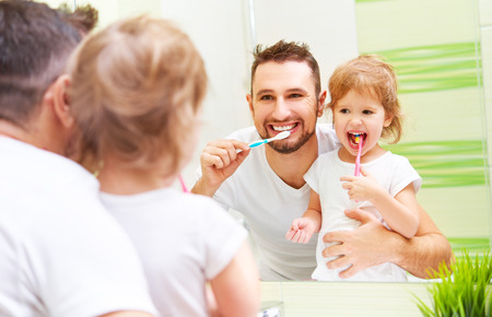 Happy family father and daughter child girl brushing her teeth in the bathroom toothbrushes Standard-Bild