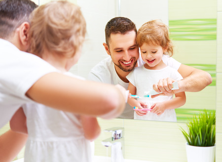 Happy family father and daughter child girl brushing her teeth in the bathroom toothbrushes 스톡 콘텐츠