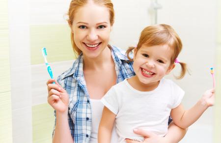 Mère de famille heureuse et sa fille enfant fille se brosser les dents brosses à dents devant le miroir dans la salle de bains Banque d'images - 48764501