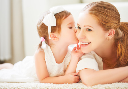 white day: happy family.  Little child girl kisses her mom