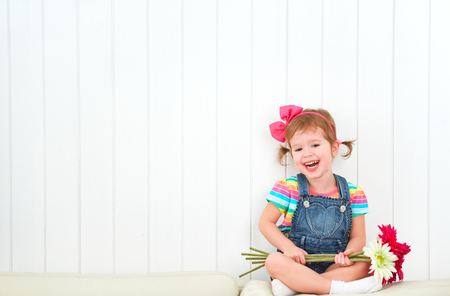 green plants: Happy  child laughing little girl with a bouquet of gerbera flowers in the empty white wall Stock Photo