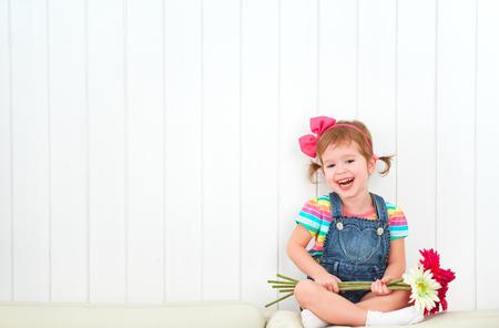ni�as peque�as: Ni�o feliz riendo ni�a con un ramo de flores de gerbera en la pared blanca vac�a