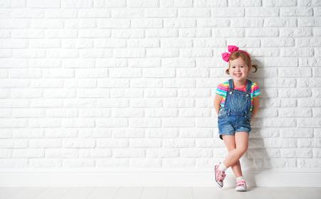 moda: Criança feliz garotinha rindo de uma parede de tijolo vazio em branco
