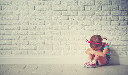작은 아이 우는 소녀와 빈 벽돌 벽에 대한 슬픈