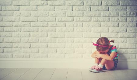 vagabundos: niña niño llorando y triste sobre una pared de ladrillo vacía Foto de archivo