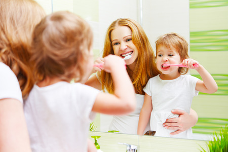 routine: mother and daughter child girl brushing her teeth toothbrushes front of the mirror in the bathroom