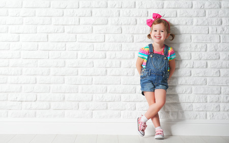 Happy child little girl laughing at a blank empty brick wall