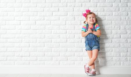 pequeño: Niño feliz niña riendo de una pared de ladrillo vacío en blanco