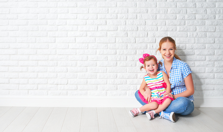 concept happy family mother and baby daughter, a girl at a blank brick wall of a house move Banque d'images