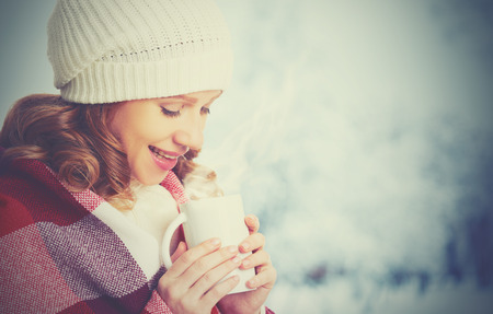 happy woman with a cup of hot drink on a cold winter outdoors