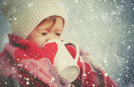 추운 겨울 야외에서 뜨거운 음료 한잔과 함께 행복 한 아이 소녀