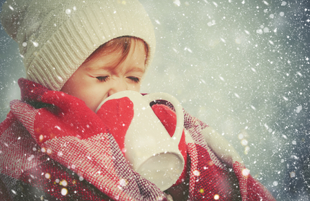 happy child girl with a cup of hot drink on a cold winter outdoors
