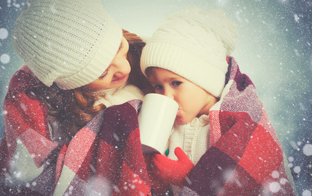 hot cold: happy family mother and child daughter drinking hot tea on a winter walk outdoors Stock Photo