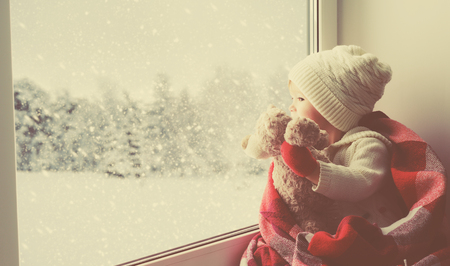 child little girl sitting by the window with a teddy bear and looking at the winter forest 스톡 콘텐츠