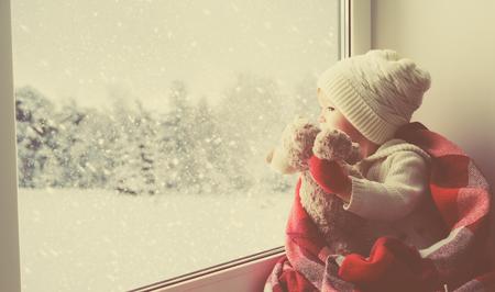 Kind kleines Mädchen sitzt am Fenster mit einem Teddybär und Blick auf den Winterwald