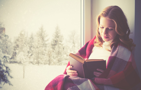 winter woman: happy girl reading a book by the window in the winter Stock Photo