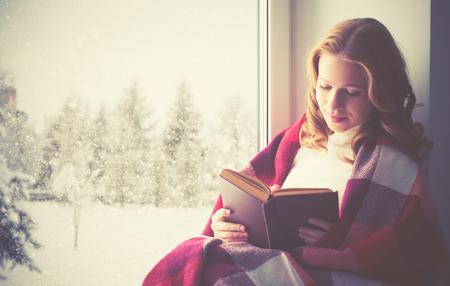 personas leyendo: niña feliz leyendo un libro junto a la ventana en el invierno Foto de archivo