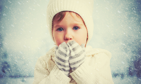 cold season: child face of a little girl in nature in winter outdoors Stock Photo