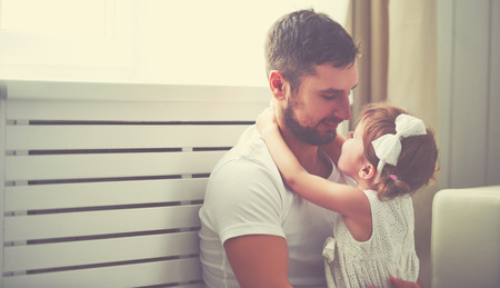 dad and daughter: happy family child baby girl in the arms of his father at home window