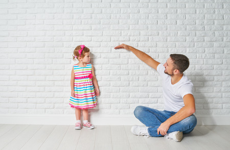 concept. Dad measures the growth of her child daughter at a blank brick wall Stockfoto