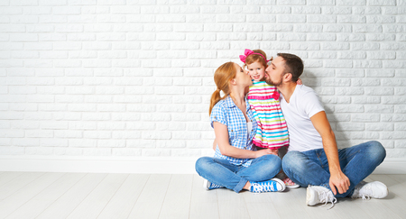 concept of mortgage housing problems. family mother father child daughter at a blank white brick wall