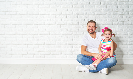 housing problems: concept of mortgage housing problems. Family father child daughter at a blank white brick wall