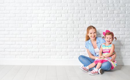 casita de dulces: concepto de madre feliz de la familia y su hija bebé, una niña en una pared de ladrillo blanco de una mudanza Foto de archivo