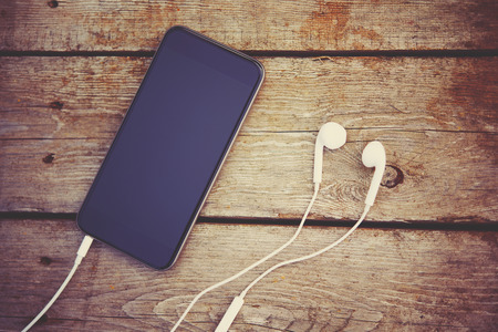 ear phones: cell phone and headphones lay on an old wooden table Stock Photo