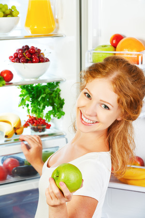 healthy foods: Happy woman with apple standing at the open refrigerator with fruits, vegetables and healthy food