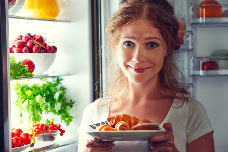 refrigerator with food: woman eats sweets at night to sneak in a refrigerator