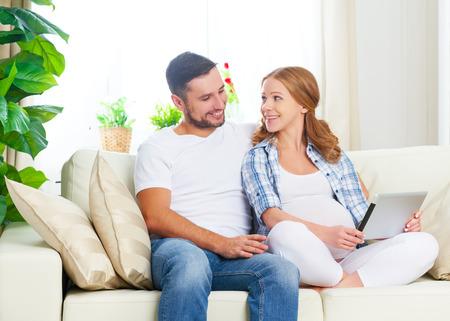 trabajando en casa: Padres felices que esperan malyshayu mam� embarazada y pap� con tablet PC en el sof� en casa Foto de archivo