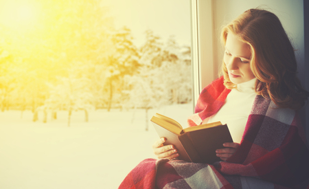 cute blonde: happy girl reading a book by the window in the winter Stock Photo