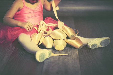 pointe: legs a little ballerina with ballet pointe shoes and pink skirt tutu on a dark background Stock Photo