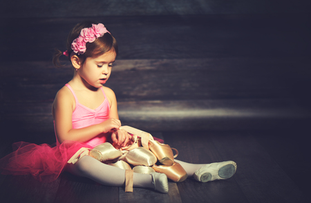 little child ballerina with ballet pointe shoes and pink skirt tutu on  dark background