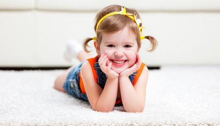 girl lying: Happy little girl lying on the floor at home Stock Photo