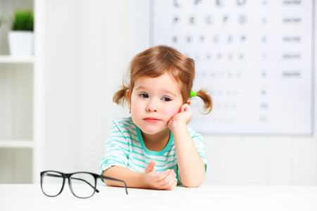 myopia: concept vision testing. child  girl with eyeglasses at the doctor ophthalmologist