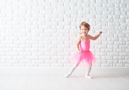 little child girl dreams of becoming  ballerina in a pink tutu skirt Foto de archivo