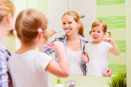 routine: happy family mother and daughter child girl brushing her teeth toothbrushes front of the mirror in the bathroom Stock Photo