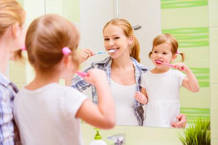 dientes sanos: madre de familia feliz y la hija niña niño cepillándose los dientes cepillos de dientes frente al espejo en el baño