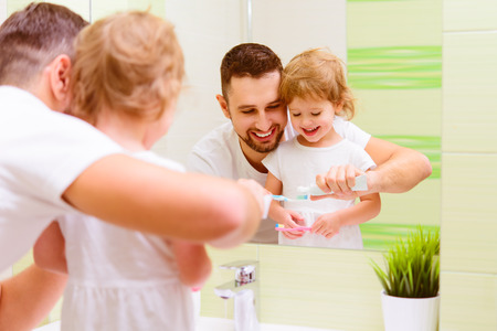 Happy family father and daughter child girl brushing her teeth in the bathroom toothbrushes Stock Photo