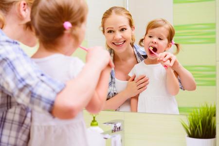 madre e hija: madre de familia feliz y la hija niña niño cepillándose los dientes cepillos de dientes frente al espejo en el baño