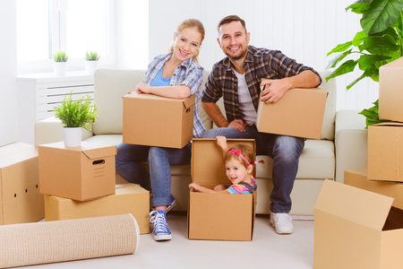 people moving: moving to a new home. Happy family with cardboard boxes